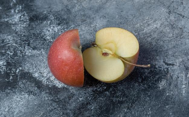Maçã vermelha fresca cortada em um fundo de mármore.