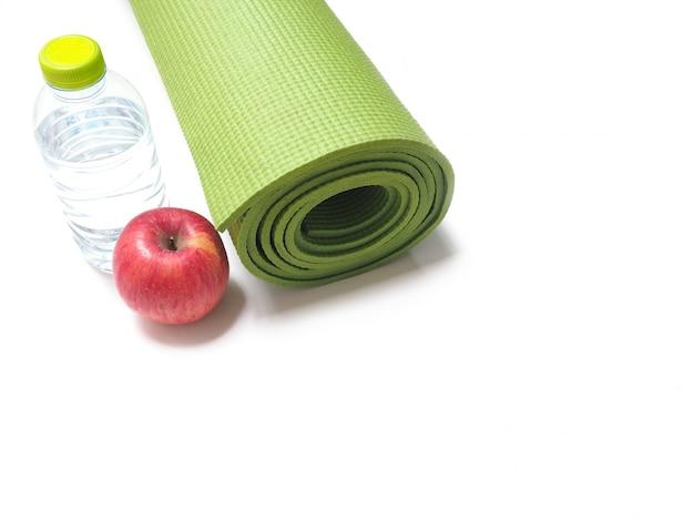 Maçã vermelha, garrafa de água e tapete de ioga