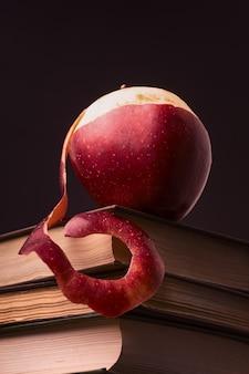 Maçã vermelha madura em cima de livros empilhados em um fundo preto