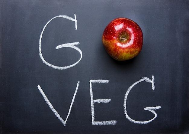 Maçã vermelha na mão de lousa preta lettering go veg. dieta saudável do conceito vegetariano vegetariana