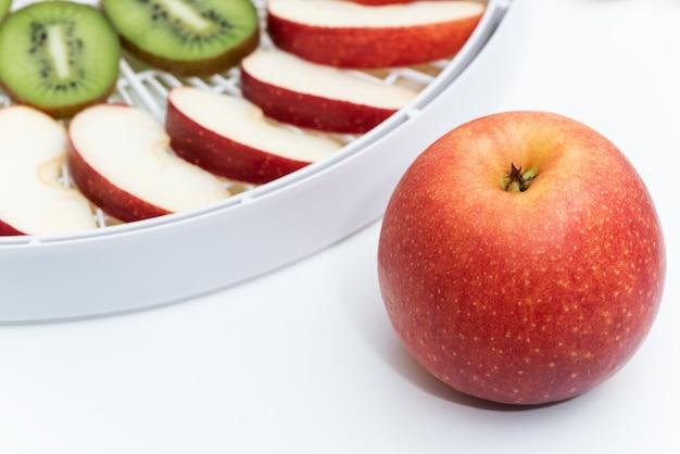 Maçã vermelha no fundo de uma bandeja do desidratador com fatias de maçãs.