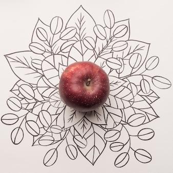 Maçã vermelha sobre fundo floral de contorno
