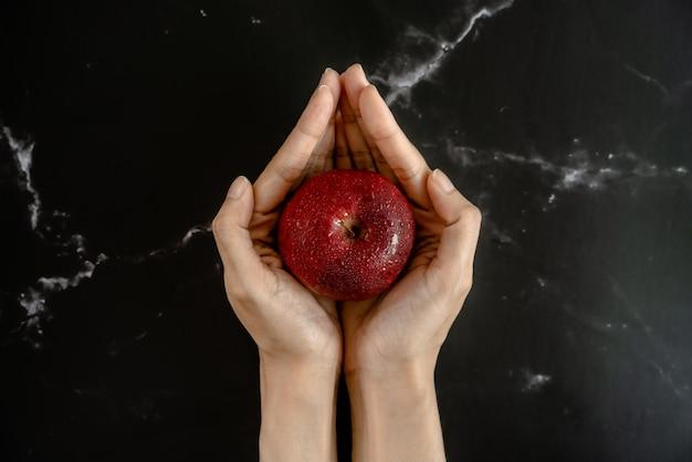 Maçã vermelha suculenta fresca com gotas de spray de água na maçã nas mãos em forma de lótus segurando uma superfície de mármore preto