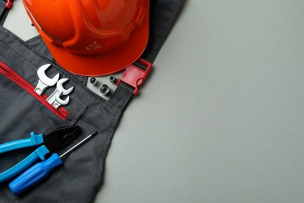 Macacão, capacete e ferramentas em cinza claro