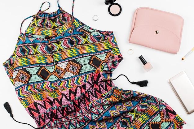 Macacão colorido, smartphone, maquiagem de produtos e acessórios em fundo branco.