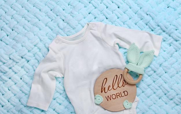 Macacão de bebê branco brinquedos de madeira tablet de madeira hello world em fundo azul xadrez macio