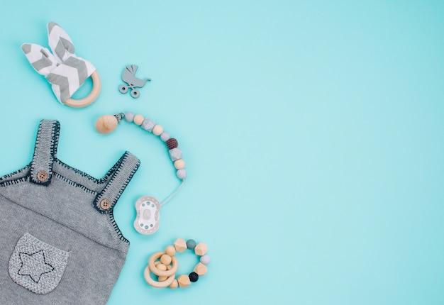 Macacão de bebê, chupeta e brinquedos de madeira em azul