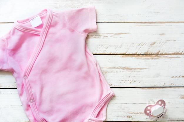 Macacão de bebê rosa sobre fundo branco de madeira com com copyspace.