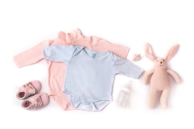 Macacão de bebê, sapatos, mamadeira, chupeta e coelhinho de brinquedo isolado no fundo branco