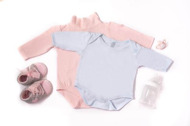 Macacão de bebê, sapatos, mamadeira e chupeta isolados no fundo branco