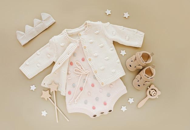 Macacão de malha pastel com macacão e sapatos, coroa de algodão e brinquedos. conjunto de roupas de bebê e acessórios para a princesinha em fundo bege. recém-nascido da moda. camada plana, vista superior