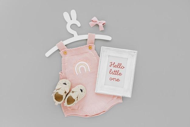 Macacão de malha rosa em cabide bonito com orelhas de coelho com moldura de foto e botas de bebê. conjunto de roupas infantis e acessórios para o verão. recém-nascido da moda. camada plana, vista superior