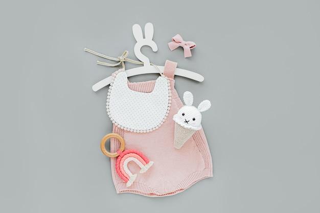 Macacão de malha rosa em cabide fofo com orelhas de coelho com babador, sorvete de brinquedo e óculos escuros. conjunto de roupas de bebê e acessórios para o verão. recém-nascido da moda. camada plana, vista superior