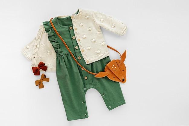 Macacão verde com blusão de malha, bolsa infantil. conjunto de roupas e acessórios de bebê. roupa de moda infantil. camada plana, vista superior