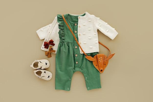 Macacão verde com blusão de malha, bolsa infantil e bota de bebê. conjunto de roupas e acessórios de bebê. roupa de moda infantil. camada plana, vista superior