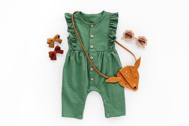 Macacão verde com bolsa infantil e óculos escuros. conjunto de roupas de bebê e acessórios para a primavera ou verão. roupa de moda infantil. camada plana, vista superior