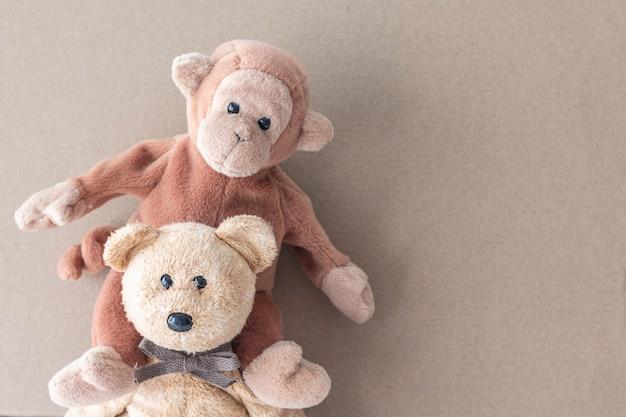 Macaco e urso de pelúcia na superfície marrom