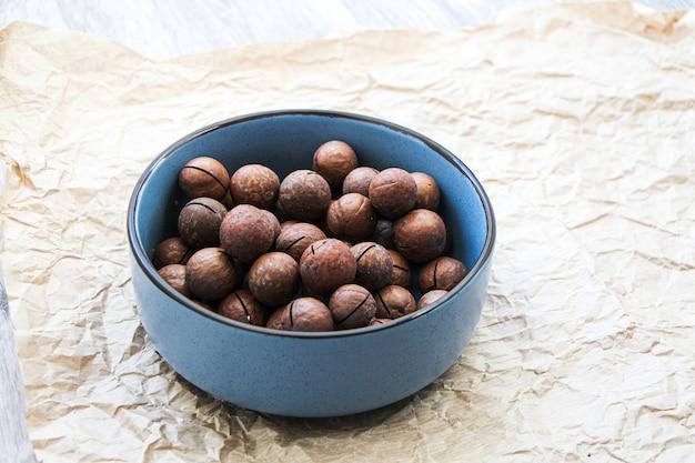 Macadâmia em uma tigela de cerâmica azul sobre fundo de papel vegetal. conceito de comida saudável orgânica