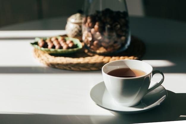 Macadâmia em uma tigela e uma xícara de chá ou café fica na mesa da cozinha, luz da manhã