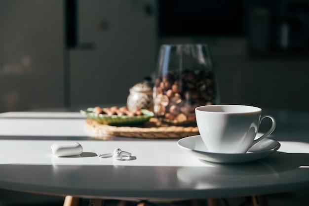 Macadâmia em uma tigela, xícara de chá ou café e fones de ouvido estava na mesa da cozinha, luz da manhã