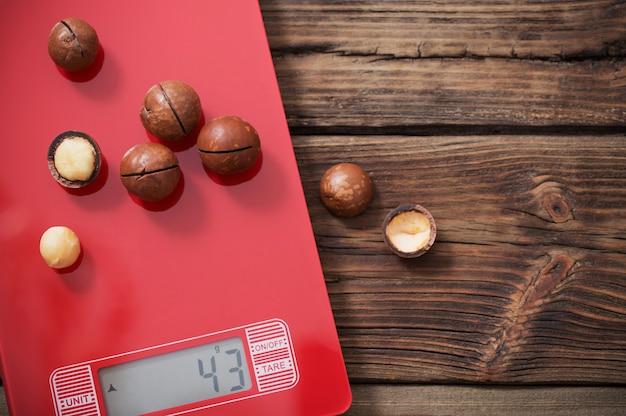 Macadâmia na balança de cozinha vermelha em fundo de madeira