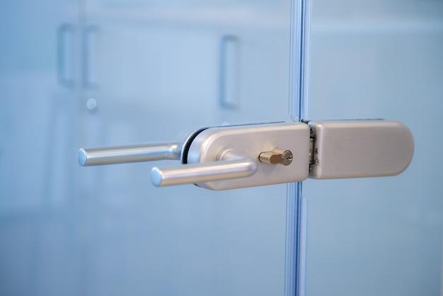 Maçaneta da fechadura da porta de vidro no escritório comercial.