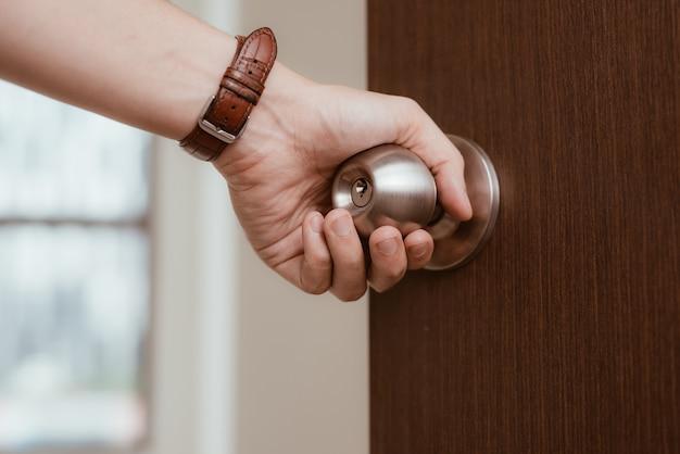 Maçaneta da porta aberta com mão masculina ou abrindo a porta