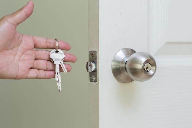 Maçaneta da porta com a chave na mão