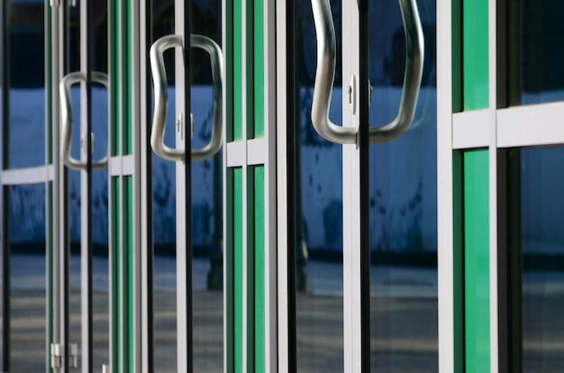 Maçaneta da porta cromada e vidro da fachada de escritório em alumínio moderno