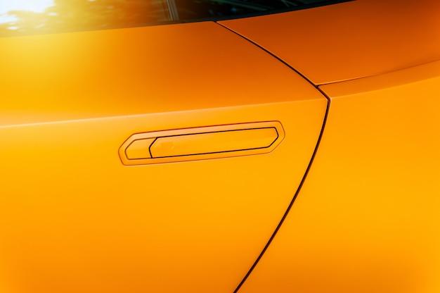 Maçaneta da porta de carro de um carro moderno laranja