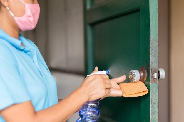 Maçaneta da porta de limpeza de mulher com spray de álcool para prevenção de covid-19.