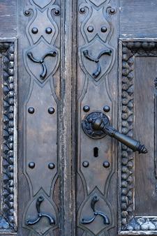 Maçaneta da porta de metal velha na porta velha.