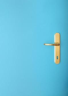 Maçaneta da porta de ouro sobre um fundo azul. conceito mínimo de natureza morta com grande espaço de cópia. estilo plano leigo de fotografia mínima.