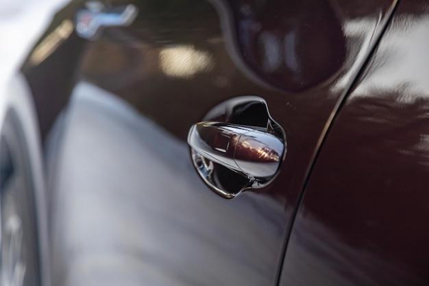 Maçaneta da porta do carro com entrada sem chave, a carroceria do carro é escura na cor preta. porta do motorista de um