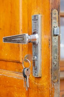 Maçaneta da porta velha com fechadura e chaveiro na porta de madeira aberta.