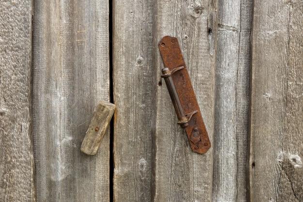 Maçaneta de ferro em parede de madeira a porta é fechada com trava de madeira
