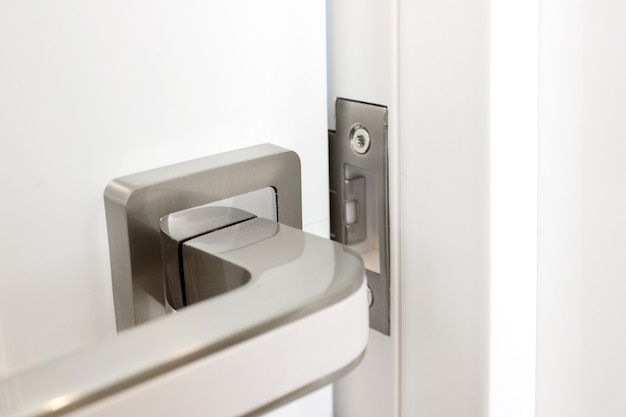 Maçaneta de metal moderna em detalhes interiores de close-up de porta branca.