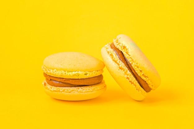 Macaron amarelo colorido de amêndoa doce ou bolo de sobremesa macaroon isolado no fundo amarelo na moda moderno.