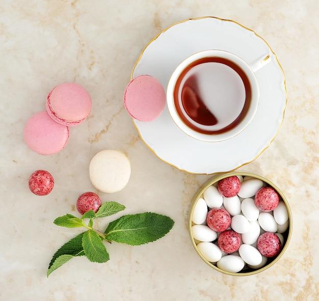 Macaron colorido com uma xícara de chá