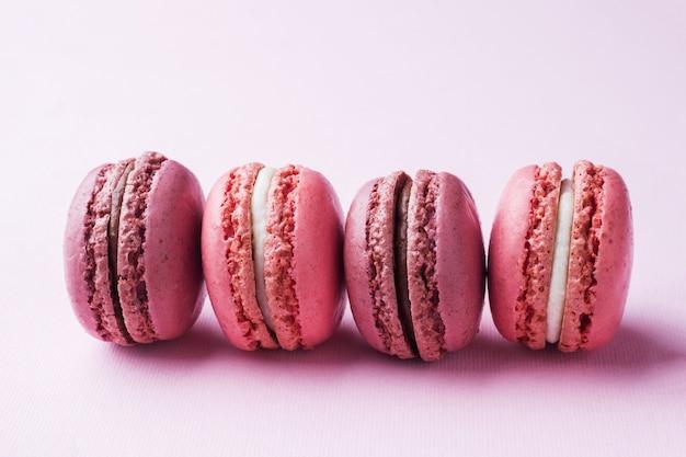 Macaron de sobremesa-de-rosa ou macaroons em fundo rosa