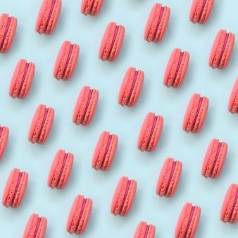 Macaron ou bolinho de amêndoa cor-de-rosa do bolo da sobremesa na opinião superior do fundo azul pastel na moda.