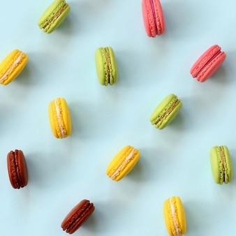 Macaron ou bolinho de amêndoa do bolo da sobremesa na opinião superior do fundo azul pastel na moda. composição plana leiga