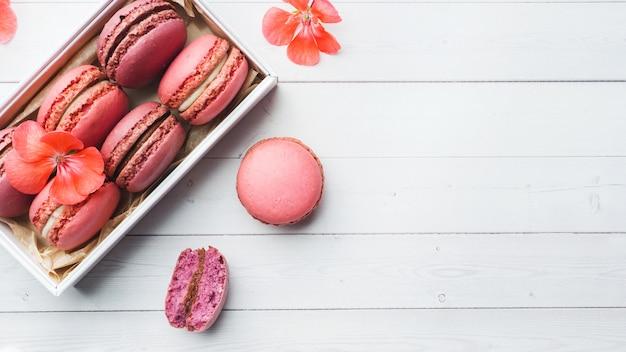 Macaron ou macaroons cor-de-rosa da sobremesa em uma caixa em uma tabela branca. copie o espaço.