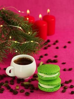 Macaron verde com fondant. perto há uma xícara de café expresso, grãos de café torrados. galho de árvore de natal com uma guirlanda e velas acesas.