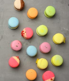 Macarons assados com sabores diferentes em um fundo de cimento cinza, vista superior