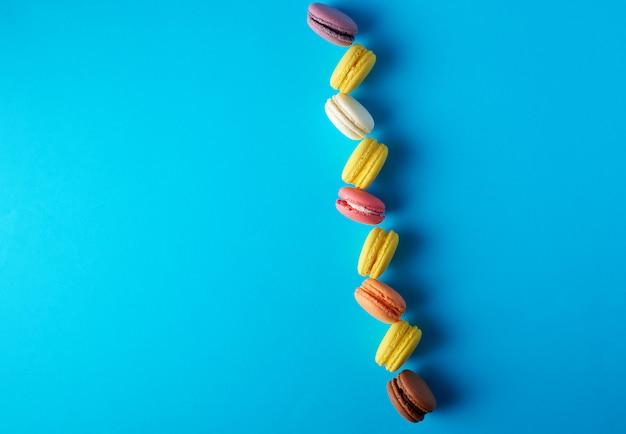 Macarons assados multicoloridos redondos com creme em uma linha