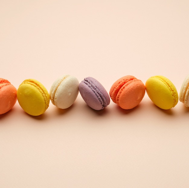 Macarons assados redondos multi coloridos com creme mentem em uma linha em uma superfície bege