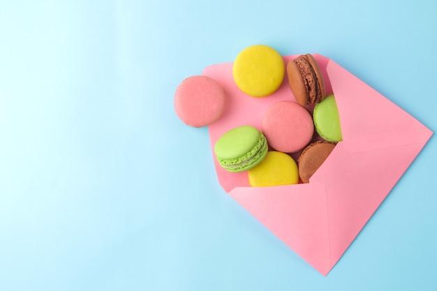 Macarons. bolinhos de macaroons multicoloridos franceses em envelope. pequeno bolo doce francês sobre fundo azul brilhante. sobremesa. doces. vista do topo.