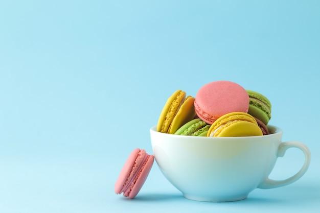 Macarons. bolinhos de macaroons multicoloridos franceses em um copo. pequeno bolo doce francês sobre fundo azul brilhante. sobremesa. doces.