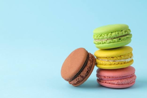 Macarons. bolos de macaroons multicoloridos franceses. pequeno bolo doce francês sobre fundo azul brilhante. sobremesa. doces.